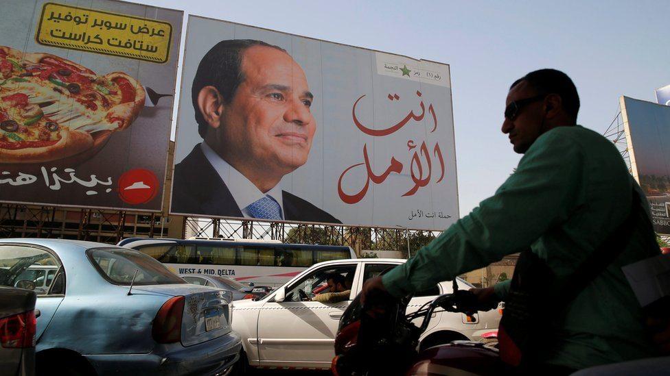 Ljudi šetaju ispred plakata egipatskoj predsednika Abdula Fateha el Sisija tokom pripreme za predsedničke izbore u Kairu, 25. marta 2018.