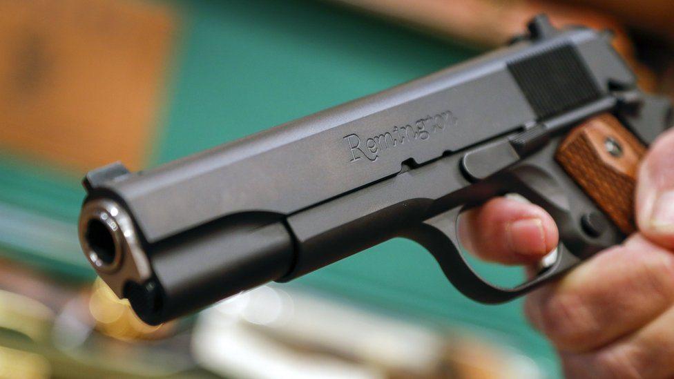 Prodavac u Atlanti drži pištolj Remington, februar 2018. godine