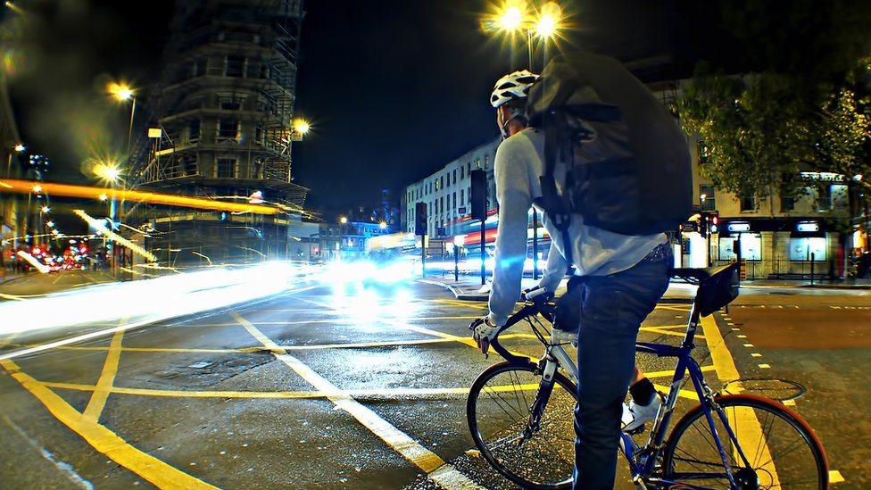 Čovek vozi bicikl u gradu, noć
