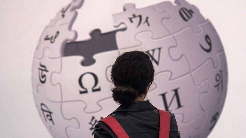 Žena stoji ispred logotipa Vikipedije