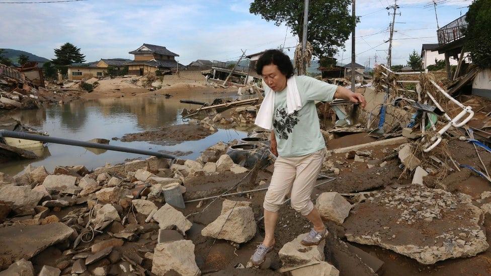 Žena hoda po ruševinama nakon poplave