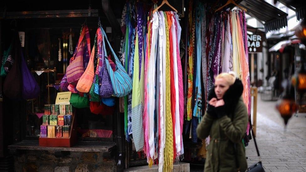 Žena šeta pored tezge sa torbama i maramama, Sarajevo