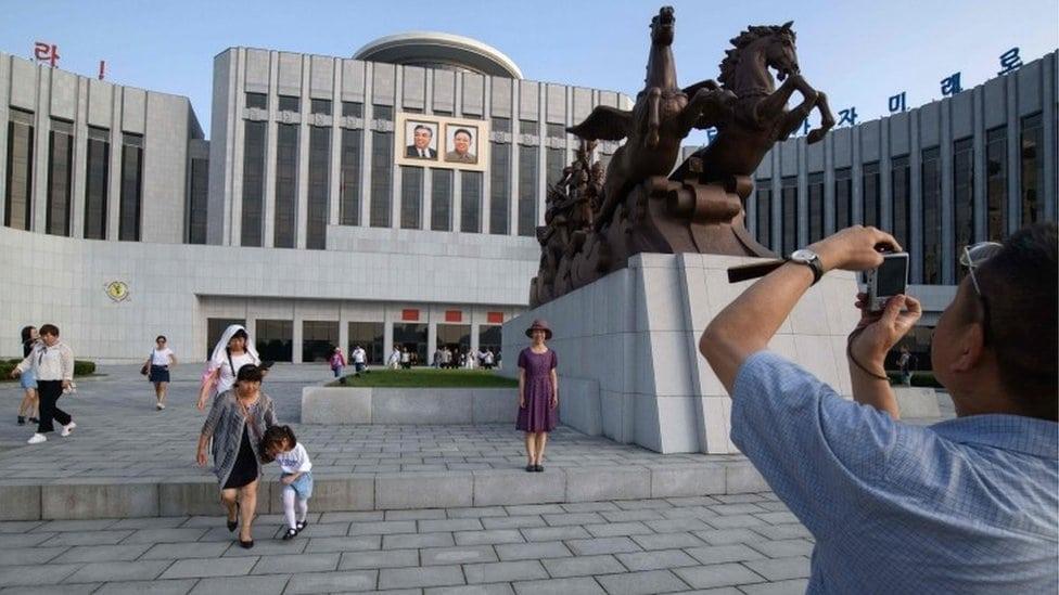 Turisti fotografišu Palatu dece u Pjongjangu
