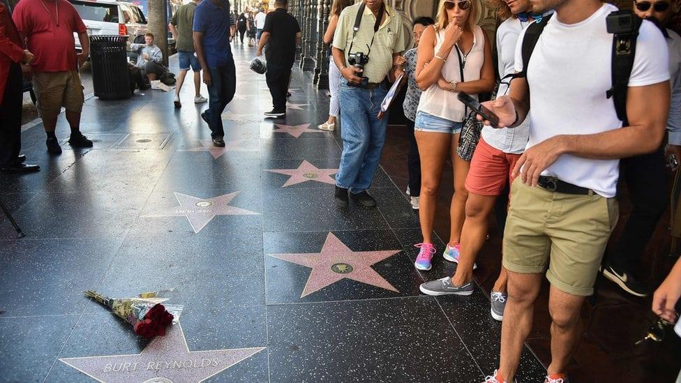 Turisti i prolaznici oko cveća koje je postavljeno na zvezdu