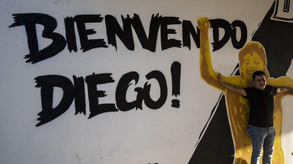 """Navijač pozira ispred murala na kome piše """"Dobrodošao Dijego"""""""