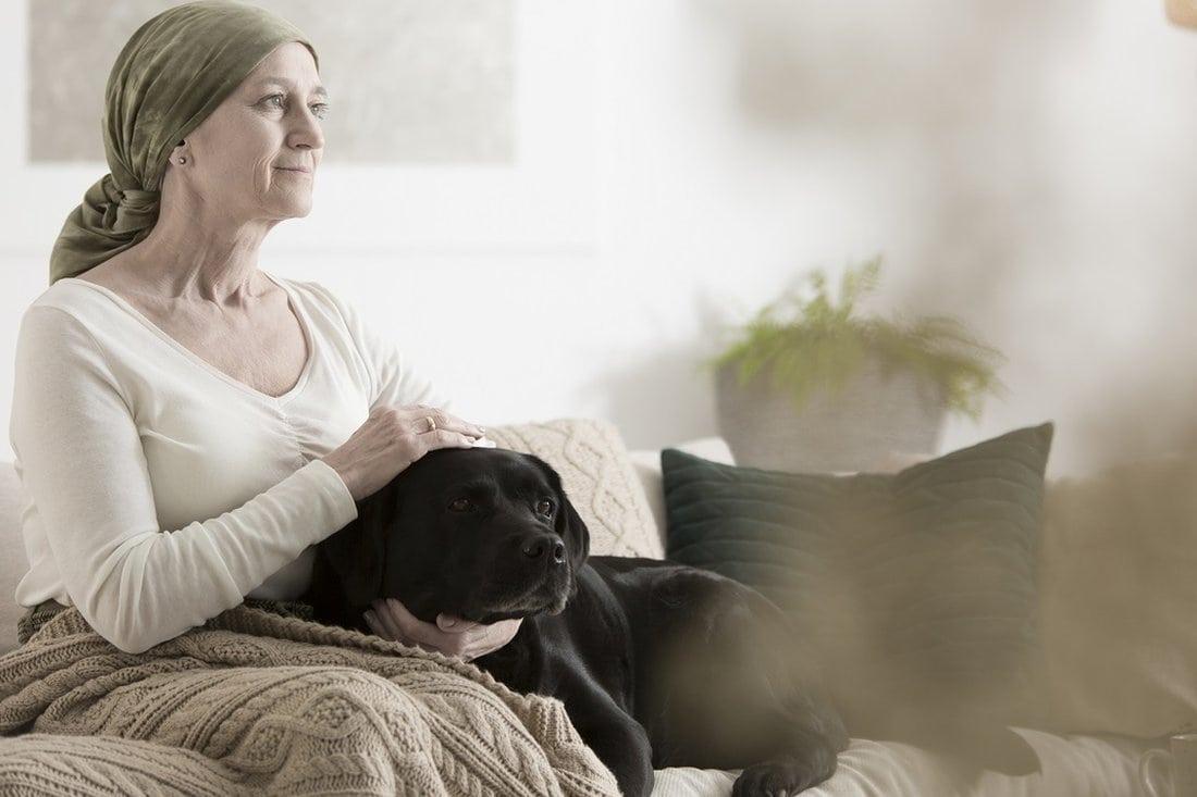 Starija bolesna žena mazi psa