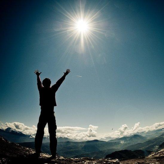 muškarac na vrhu planine
