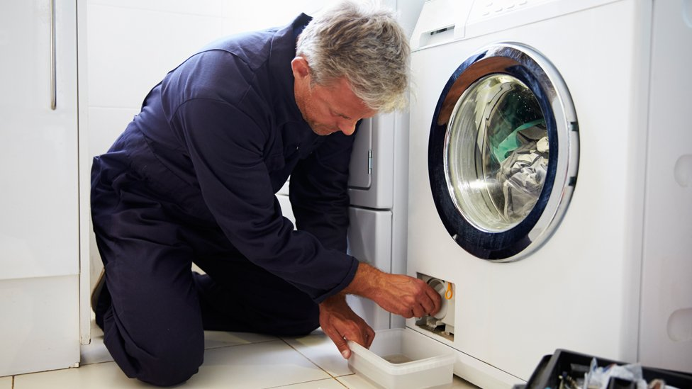 muškarac popravlja veš mašinu