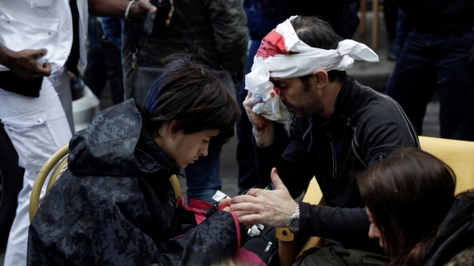 An injured man with a bloodied bandage round his head