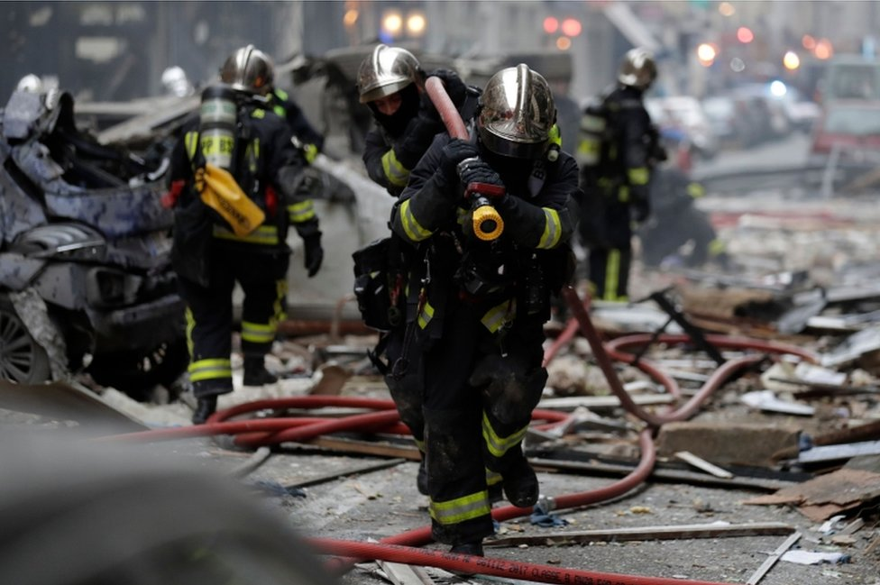 French firefighters in helmets run with a hose near a Paris bakery on the corner of the streets Saint-Cecile and Rue de Trevise