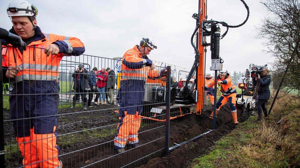 Radnici u narandžastim uniformama sastavljaju prve delove metalne ograde na granici Danse, dok ih snimatelji i fotografi slikaju