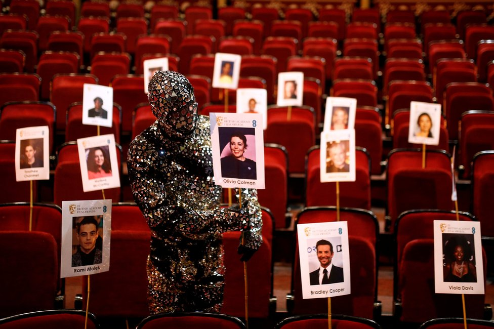 A performer in a metallic costume adjusts seat markings in a theatre