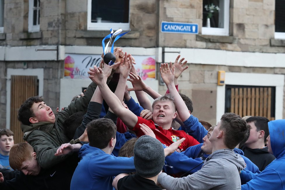 A crowd of people scramble to grab a leather ball in the street