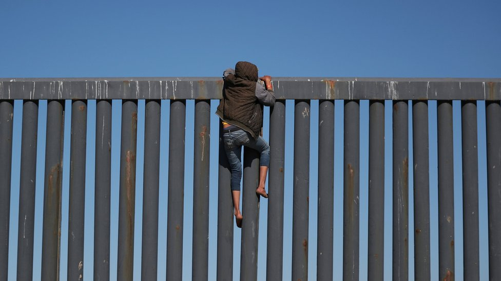 Migrant pokušava da preko ograde uđe u SAD