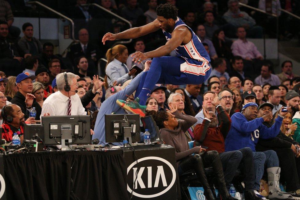 Džoel Embid skače u publiku da zadrži loptu u igri
