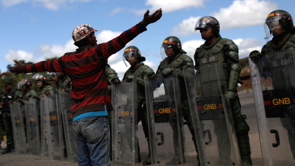 People approach Venezuelan troops at the border in the Brazilian city of Pacaraima, 22 February 2019