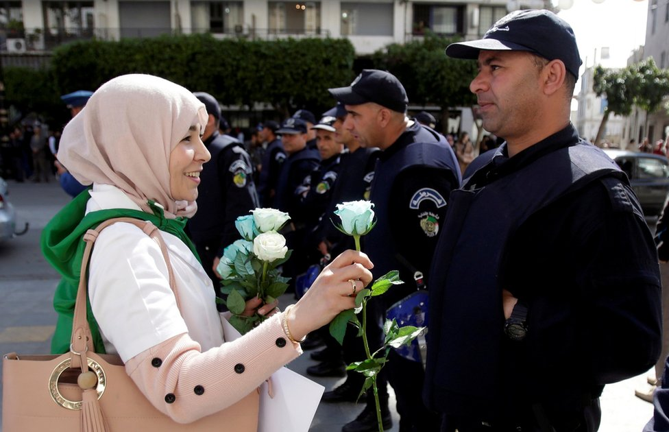 demonstrantkinja deli ruže poliicji