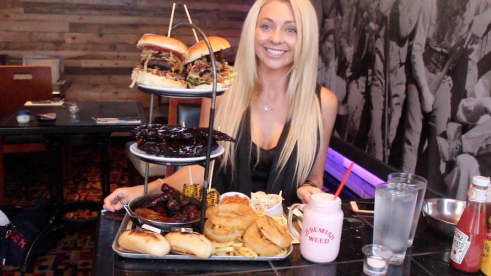 Kejt Ovens koja se profesionalno bavi blogovanjem o nadmetanjima u jelu, stoji pored velike količine hrane