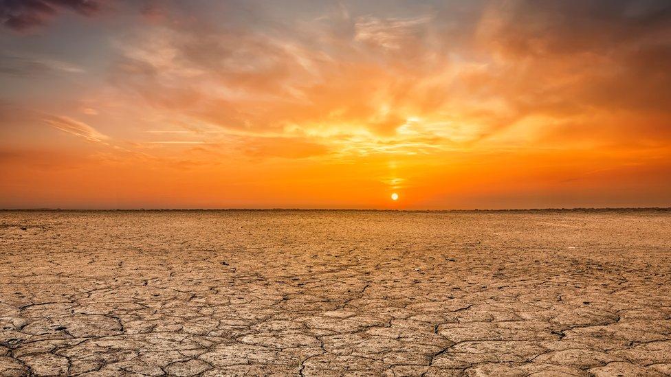 zalazak sunca i ispucala zemlja od suše