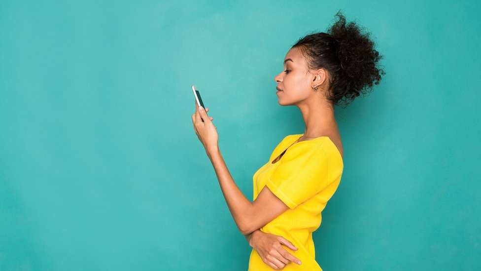 Young woman on holding a phone in her hand, on a turquoise background