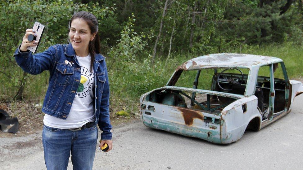 Devojka se slika ispred olupnije automobila u Zabranjenoj zoni i Černobilju