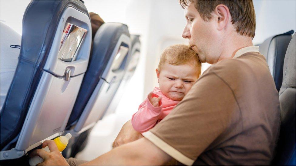 Nazadovoljna beba u tatinom krilu tokom leta