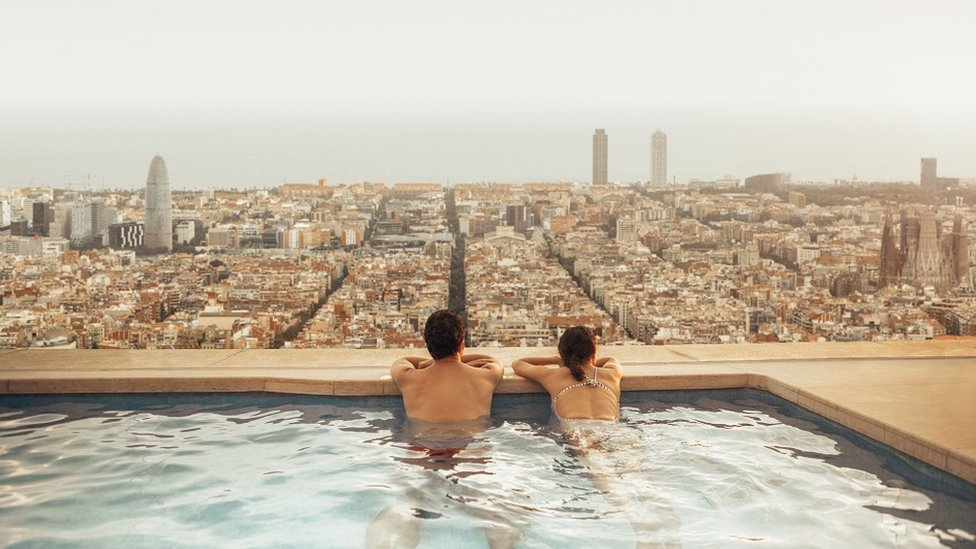 A couple on a rooftop pool in Barcelona. It's a cloudy day, and they are looking down over the city from inside an infinity pool.