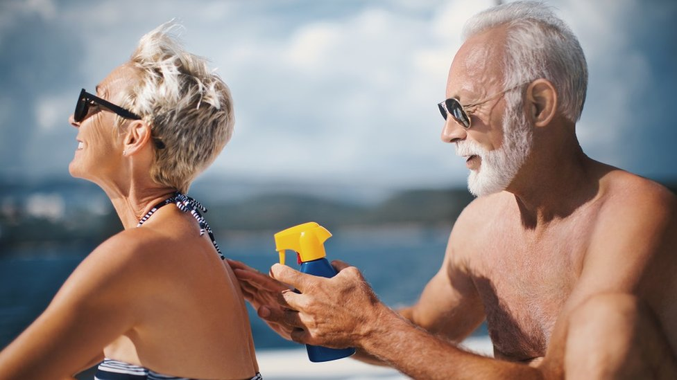 A senior couple sunbathing: the man is re-applying sunscreen on the woman.