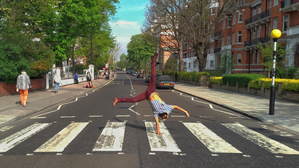 Júlio Andrade does a handstand on the Abbey Road crossing.