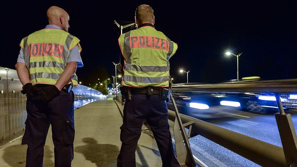 A photograph of German police officers standing by the side of a motorway at night