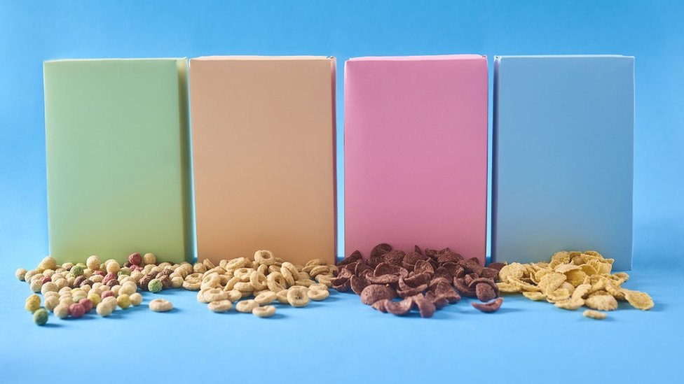 Concept image: generic colourful boxes, with different cereals on the table - blue background