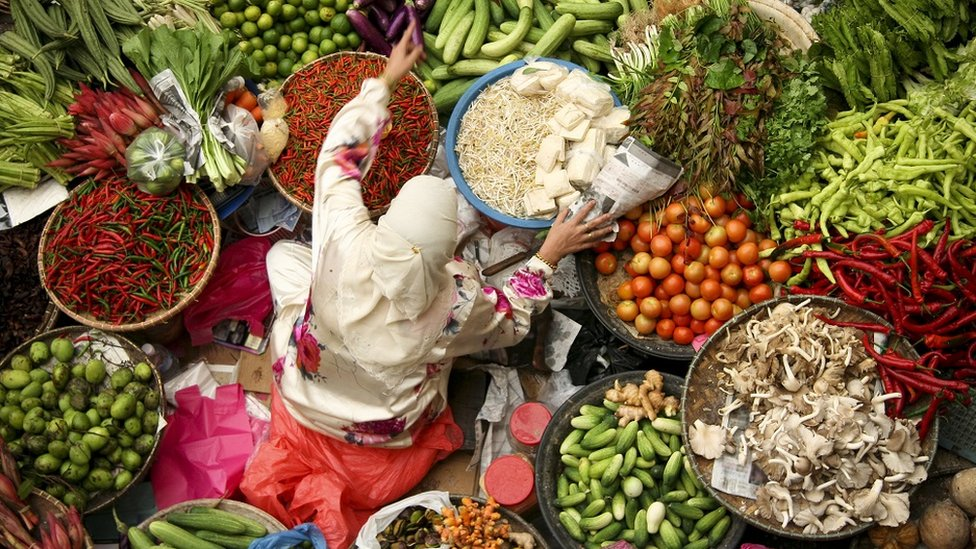 Woman selling fresh vegetables at an Asian market