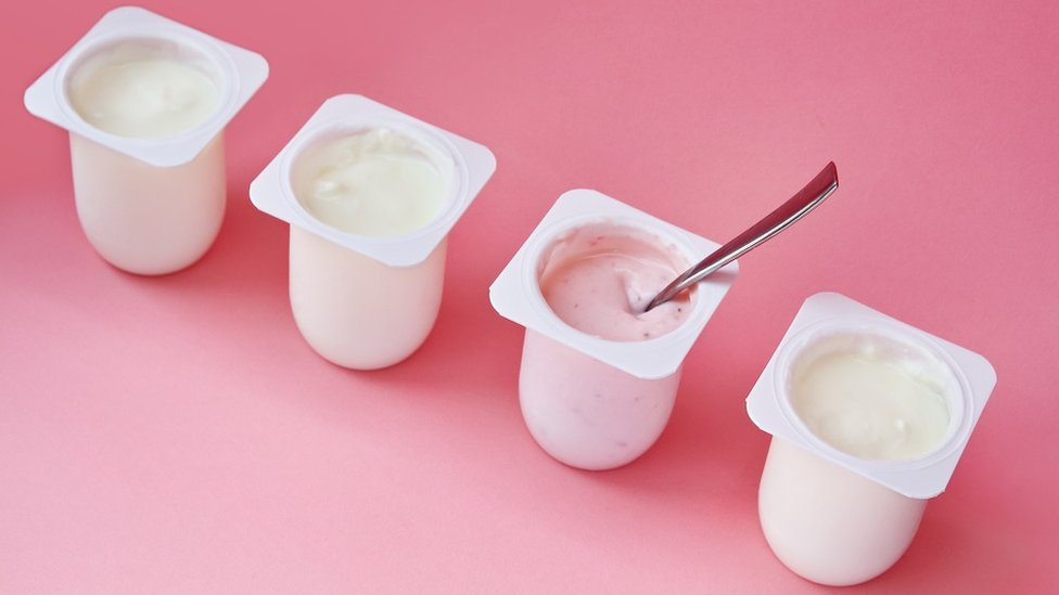 Concept image of better choice: four yogurts in white plastic cups on pink background with copy space. Strawberry pink yoghurt with spoon in it.