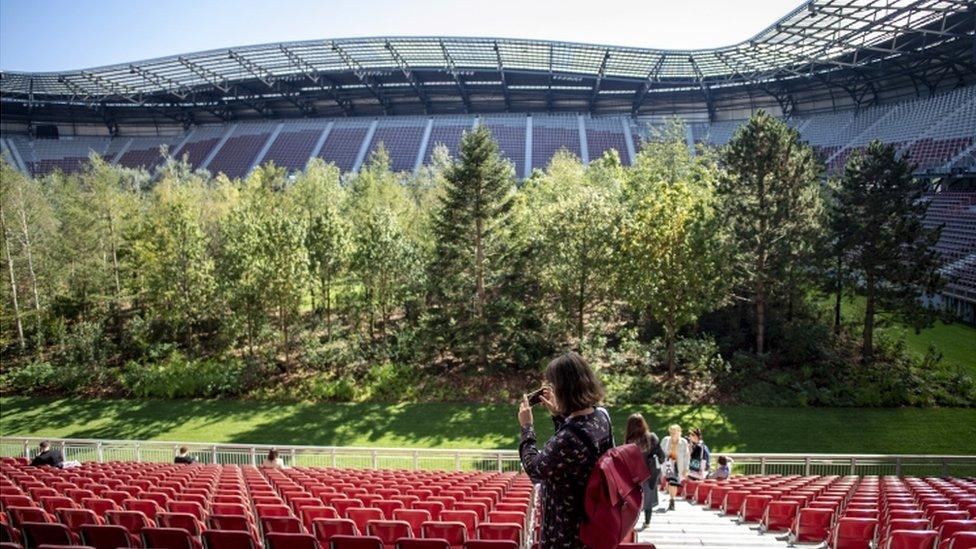 Žena fotografiše šumu na stadionu