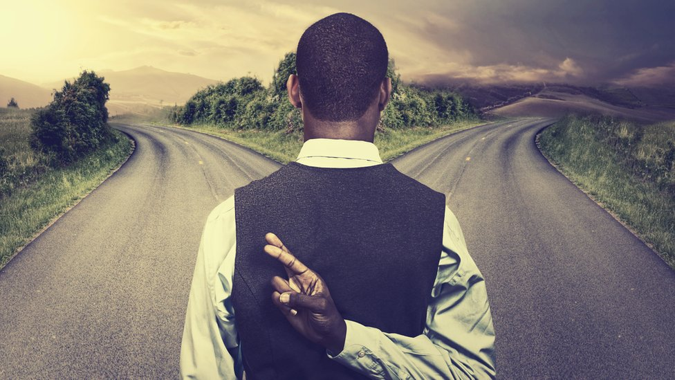 A man at a crossroads, fingers crossed behind his back.