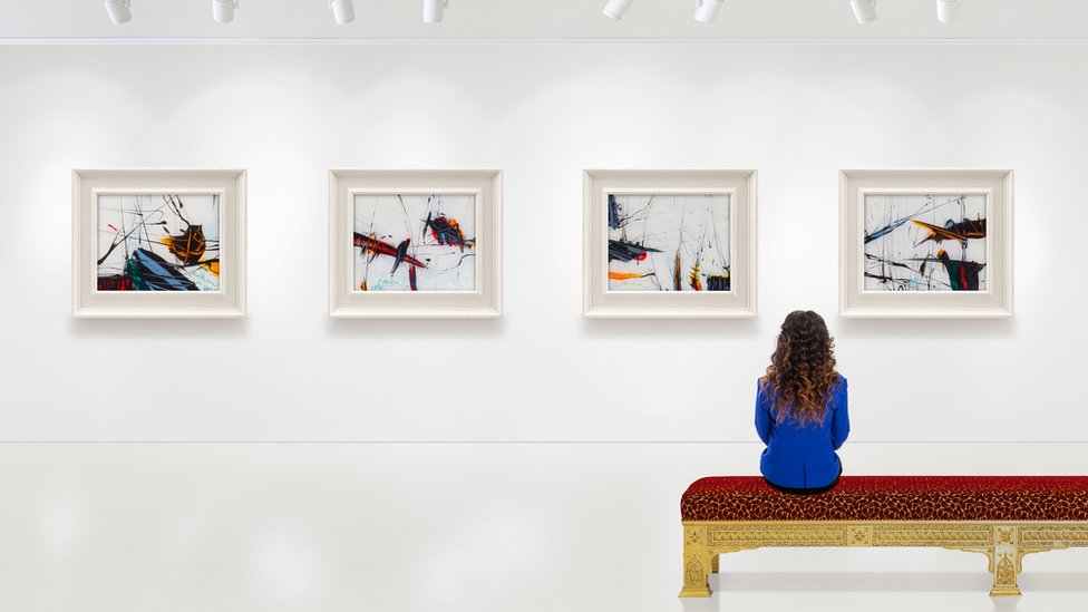 A woman sitting at an art gallery, looking at pictures - we don't know what she's thinking.