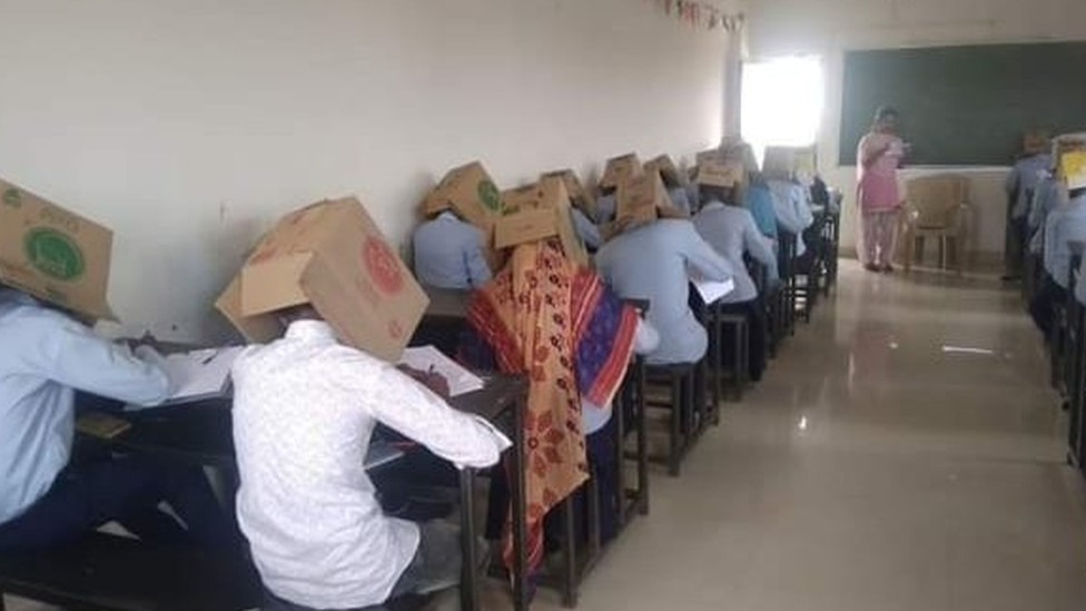 Students wearing boxes on their heads in exam