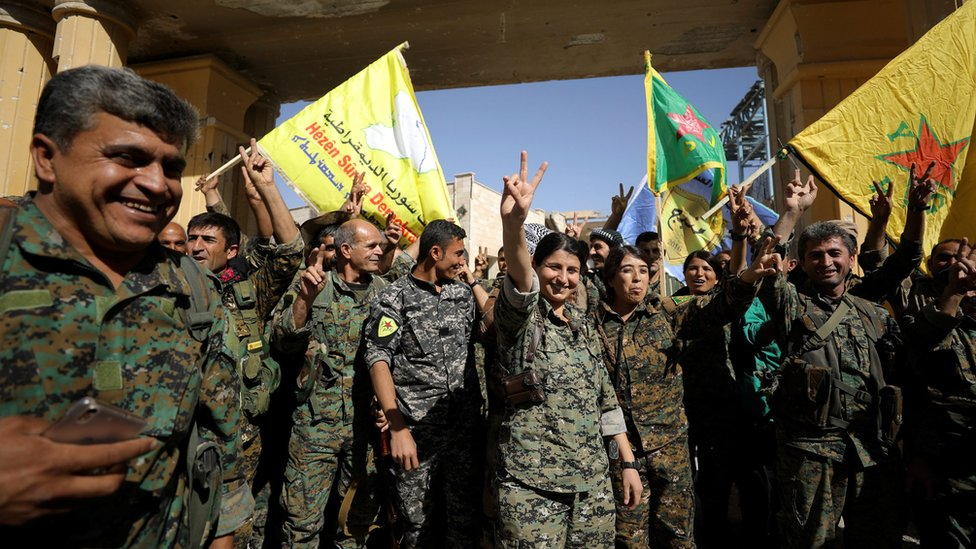Syrian Democratic Forces fighters celebrate victory against IS militants in Raqqa, Syria, on 17 October 2017