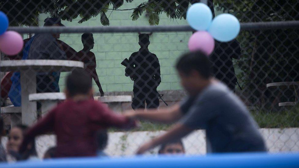 Deca se igraju na terenu, okružena naoružanim čuvarima.