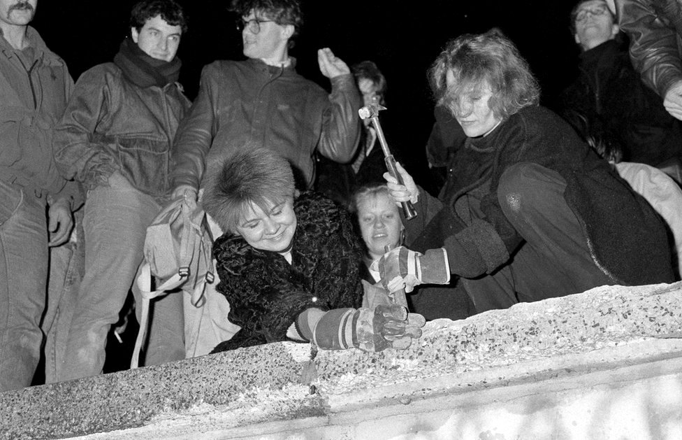 Berliners take a hammer and chisel to a section of the Berlin Wall in front of the Brandenburg Gate after the opening of the East German border was announced in Berlin on 9 November 1989