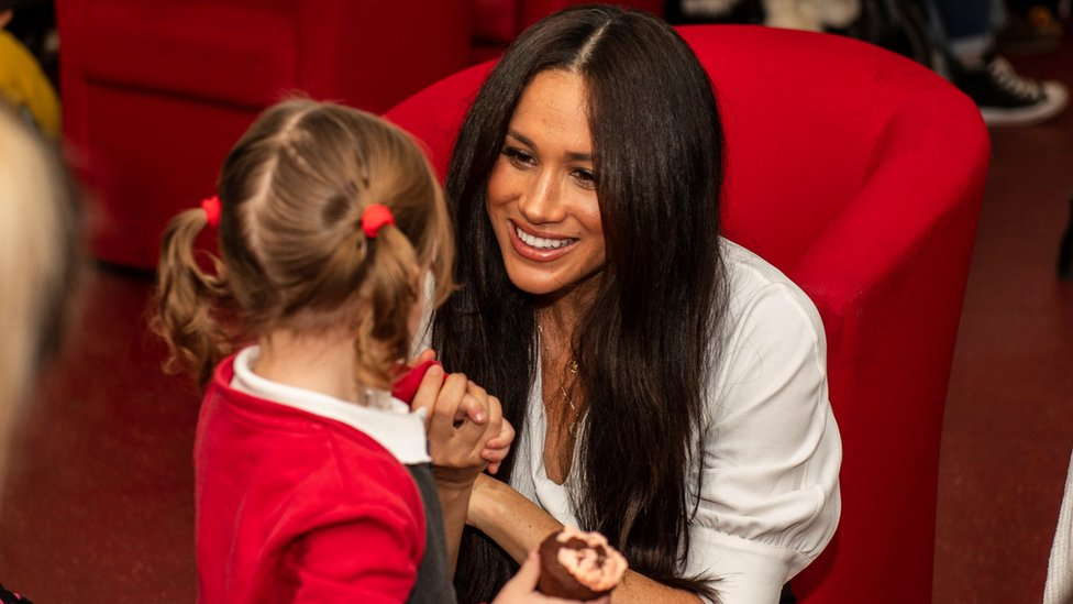The Duchess of Sussex crouches receives a cake from a little girl at Windsor's Broom Farm Community Centre