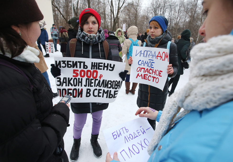 Protesters in a Moscow park - the placard on the left points out that the new fine for wife-beating is 5,000 roubles (£60)