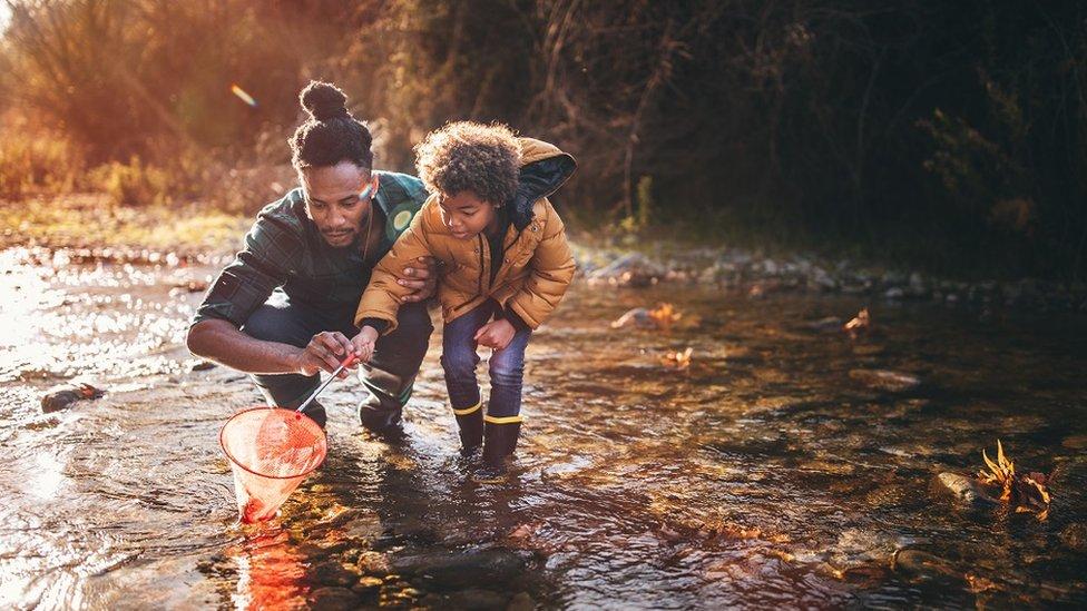 Mladi otac uči sina kako da lovi ribu mrežom