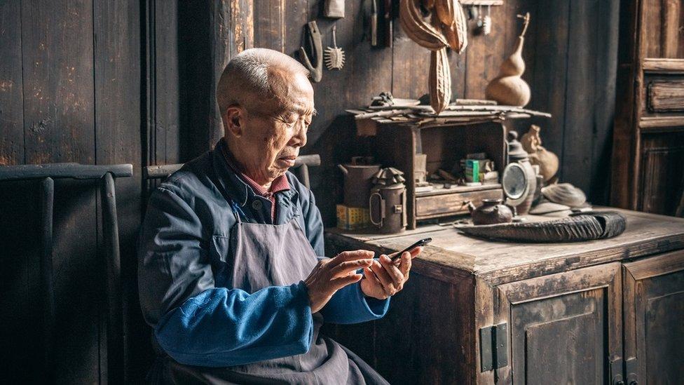 Stariji Kinez uči da skloruje na telefonu