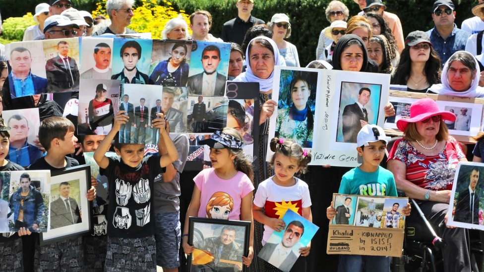 Yazidi children in Canada hold photos of family members killed by ISIS