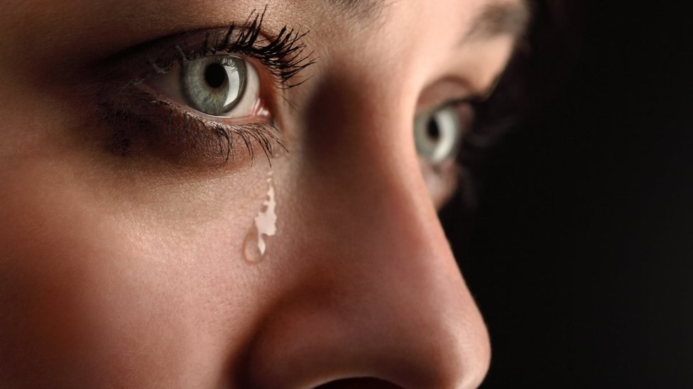 A woman's face with a tear running down her cheek