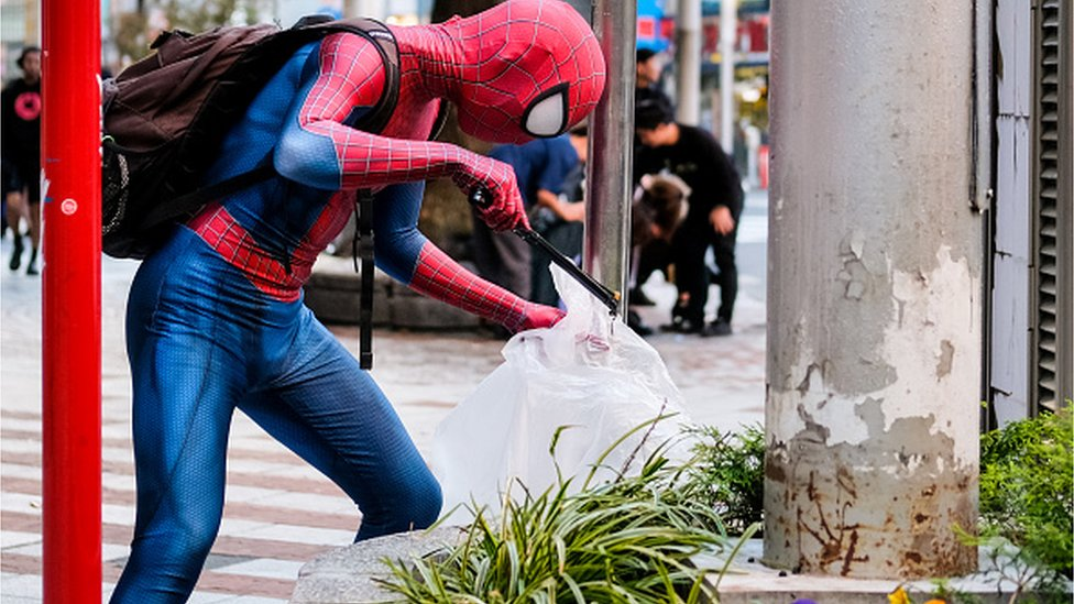 Person dressed as Spider-Man helps clean the streets the day after Halloween celebrations