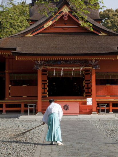 Man cleaning the gardens of a temple