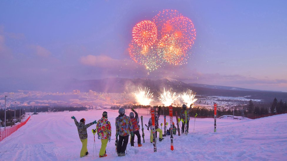 people on a skiing hill overlooking fireworks during a ribbon-cutting ceremony to open a Township of Samjiyon County