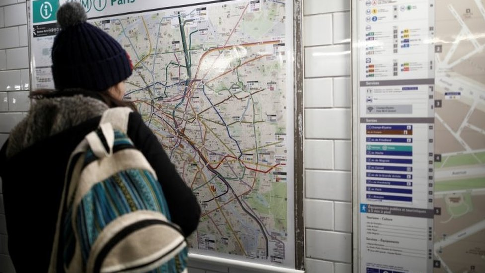 A woman looks at a map of the RATP metro lines at the Charles de Gaulle Etoile metro station